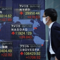 An electronic board in Tokyo shows stock prices in Tokyo and other major markets in the world. | KYODO
