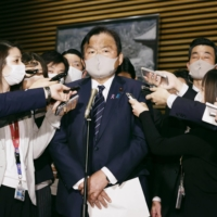 Tourism minister Kazuyoshi Akaba faces reporters in Tokyo on Nov. 24 when the government decided to temporarily exclude trips to Osaka and Sapporo from the Go To Travel subsidy program. | KYODO