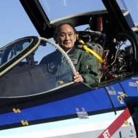 Prime Minister Yoshihide Suga sits in the cockpit of an Air Self-Defense Force F-4EJ Kai jet fighter after reviewing troops at Iruma Air Base in Sayama, northwest of Tokyo, on Saturday. | POOL / VIA AP
