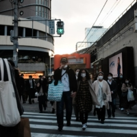 Pedestrians cross a road in front of Osaka Station on Sunday. Tokyo and Osaka last week called on some businesses to close early, while Hokkaido implemented its own measures to stem the virus's spread. | BLOOMBERG