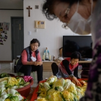 The traditional communal process of making kimchi, known as kimjang | AFP-JIJI