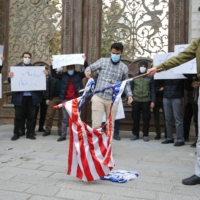 Students of Iran's Basij paramilitary force burn U.S. and Israeli flags in front of the foreign ministry in Tehran on Saturday to protest the killing of prominent nuclear scientist Mohsen Fakhrizadeh. | AFP-JIJI