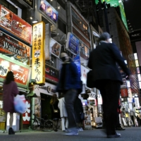 People walk in Tokyo's Kabukicho entertainment district on Friday, a day before the metropolitan government began requesting restaurants and other establishments serving alcohol to shorten business hours. | KYODO