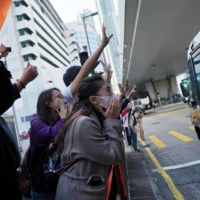 Supporters react next to a police van after the sentencing of pro-democracy activists Joshua Wong, Agnes Chow and Ivan Lam in Hong Kong on Wednesday.  | REUTERS