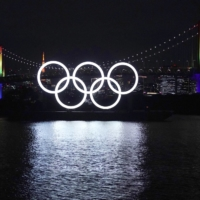 The Olympic rings float in front of Rainbow Bridge in the Odaiba district of Tokyo on Tuesday. | AP
