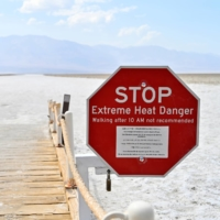 A sign alerts visitors about the extreme heat dangers at Badwater Basin, in California's Death Valley National Park, in August.  | REUTERS