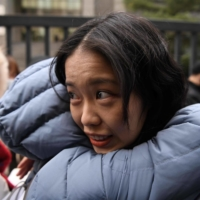 A supporter hugs Zhou Xiaoxuan outside a court in Beijing on Wednesday.  | AFP-JIJI