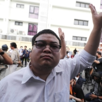 Pro-democracy activist Parit Chiwarak raises a three-finger salute, a symbol of resistance, during a protest in Bangkok on Monday.  | AP