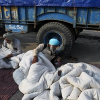 Farmers rest on mattresses at a protest site.  | REUTERS