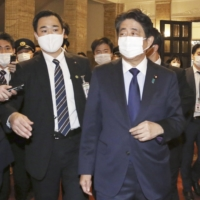 Former Prime Minister Shinzo Abe is followed by reporters after attending a Diet session on Nov. 24. | KYODO