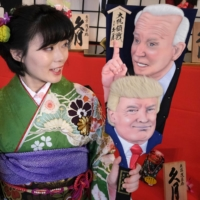 An employee of Kyugetsu displays hagoita wooden battledores decorated with images of U.S. President Donald Trump and U.S. President-elect Joe Biden, and Prime Minister Yoshihide Suga, at the company's showroom in Tokyo on Thursday. | AFP-JIJI