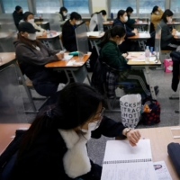 Students take university entrance exams on Thursday in Seoul.  | REUTERS