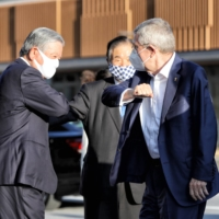 Athlete's village mayor Saburo Kawabuchi (left) bumps elbows with IOC chief Thomas Bach during an inspection of the site on Nov. 17. | POOL / VIA KYODO