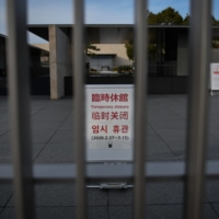 The tourism drop: A notice of temporary closure stands behind a gate at the Kyoto National Museum in March. With borders closed, the number of overseas tourists plummeted to almost zero. | BLOOMBERG