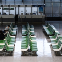 Empty halls: People sit in front of an empty service counter at Narita Airport in July.  | BLOOMBERG