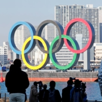 Bystanders watch as giant Olympic rings are reinstalled at the waterfront area at Odaiba Marine Park on Tuesday after they were temporarily taken down in August for maintenance. | REUTERS
