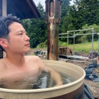 Kyohei Ueyama enjoys a hot bath on his plot of land in the mountains of Hyogo Prefecture.  | COURTESY OF KYOHEI UEYAMA