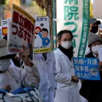 Protesters wearing masks hold banners with slogans at a rally supporting a hospital's medical workers' strike in front of the health ministry in Tokyo on Friday.   REUTERS