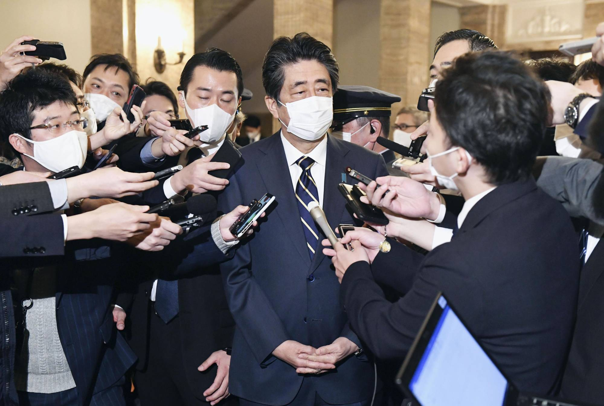 Former Prime Minister Shinzo Abe speaks to reporters in Tokyo on Friday amid allegations that his political group illegally covered shortfalls in the cost of dinners for supporters. | KYODO