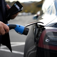 A person prepares to charge an electric vehicle (EV) at a supermarket in north London on Nov. 18. | AFP-JIJI