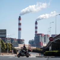 (FILES) THIS FILE PHOTO TAKEN ON MARCH 6, 2017 SHOWS A MAN RIDING HIS SCOOTER NEAR THE SHANGHAI WAIGAOQIAO POWER GENERATOR COMPANY COAL POWER PLANT IN SHANGHAI. - CHINA MUST STOP BUILDING NEW COAL POWER PLANTS AND RAMP UP ITS WIND AND SOLAR CAPACITY IF IT WANTS TO BECOME CARBON NEUTRAL BY 2060, RESEARCHERS SAID ON NOVEMBER 20, 2020. (PHOTO BY JOHANNES EISELE / AFP)