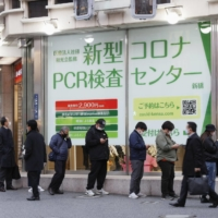 More than 40 people line up at a polymerase chain reaction (PCR) testing center that opened next to Shimbashi Station in Tokyo on Friday. The fee is ¥2,900 excluding tax. | KYODO