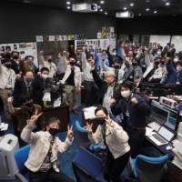 Hayabusa2 team members celebrate in the mission control room after confirming the success of a 'trajectory correction maneuver' in Sagamihara, Kanagawa Prefecture, on Saturday. | JAXA / VIA AFP-JIJI