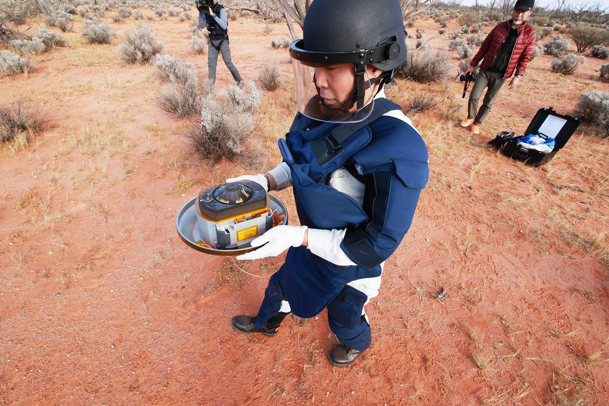 A JAXA team member recovers a capsule, carrying samples collected from a distant asteroid after being dropped off by Japanese space probe Hayabusa-2, following its landing in South Australia. | JAXA / VIA AFP-JIJI