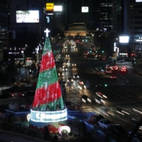 A Christmas tree is lit during a ceremony at Seoul City Hall Plaza on Saturday.  | AP