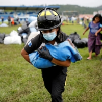 A firefighter carries a baby rescued along with her mother from an area affected by mudslides in San Cristobal Verapaz, Guatemala, on Nov. 7. | REUTERS