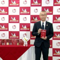 Nihon Michelin Tire Co. officials show The Michelin Guide Tokyo 2021 in Tokyo on Monday. | KYODO