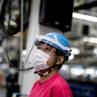 An employee works on a Mitsubishi assembly line in Kawasaki on May 18. | REUTERS