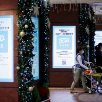 Electric advertising signboards display ads affiliated with the Go To Travel campaign, a government-backed discount program encouraging domestic travel to help boost the economy, at a train station in Tokyo on Nov. 25. | REUTERS