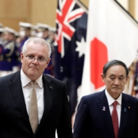 Prime Minister Yoshihide Suga and his Australian counterpart, Scott Morrison, review an honor guard at Suga's official residence in Tokyo on Nov. 17. | POOL / VIA REUTERS