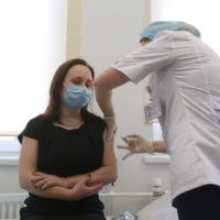 A health worker administers the Sputnik V COVID-19 vaccine, at a clinic in Moscow on Saturday.  | BLOOMBERG