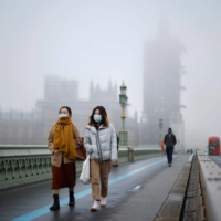 Pedestrians cross Westminster Bridge as fog envelopes the Palace of Westminster in London on Tuesday.  | AFP-JIJI