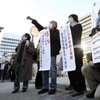 Plaintiffs who claimed that two reactors at the Oi nuclear power plant are vulnerable to a major earthquake applaud in front of the Osaka District Court on Friday, after the court nullified the government's judgment that they meet required safety levels. | KYODO