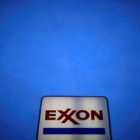 An Exxon gas station. Exxon produces more carbon dioxide than it can sell or use, so the company lets a lot float away — as much as 300,000 cars' worth of emissions a year. | REUTERS