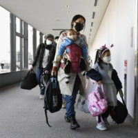 Passengers from a flight from China walk through Narita International Airport in November. The government will establish in March a center for monitoring the health condition of visitors from overseas during their stay. | KYODO