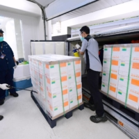 Workers spray disinfectant on boxes containing experimental coronavirus vaccines made by Chinese company Sinovac in Bandung, West Java, Indonesia, on Monday. | INDONESIAN PRESIDENTIAL PALACE / VIA AP