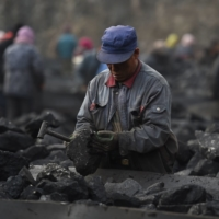 A worker sorts coal at a mine in northern China's Shanxi province. Researchers say China must stop building new coal power plants and ramp up its wind and solar capacity if it wants to become carbon neutral by 2060. | AFP-JIJI