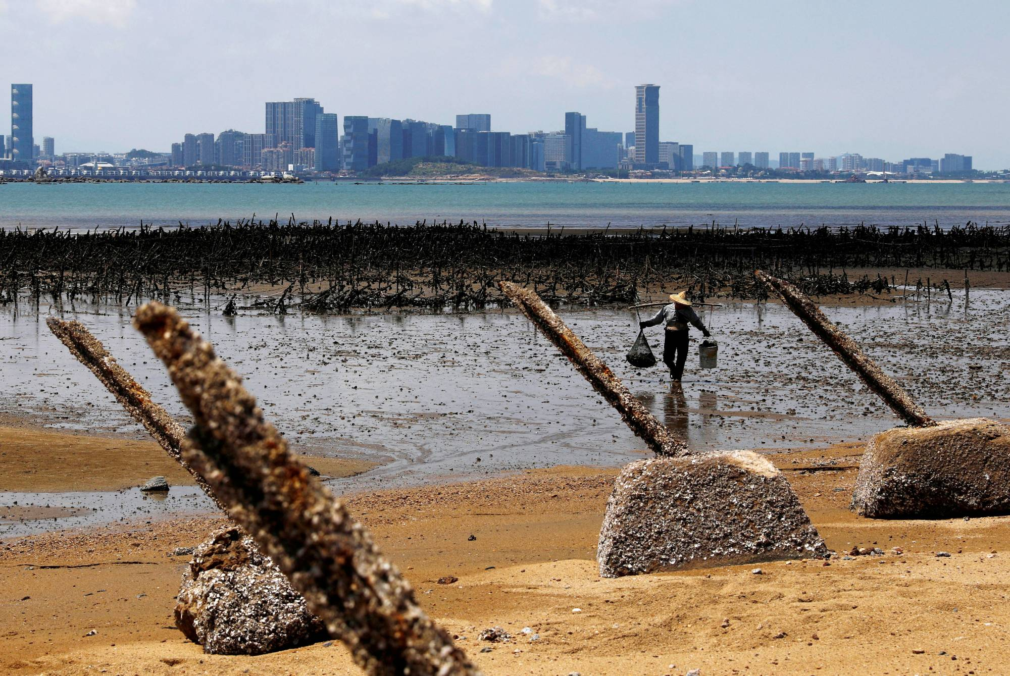 An oyster farmer walks in front of China's Xiamen, ahead of the 60th anniversary of the Second Taiwan Straits Crisis against China, on Lieyu Island, Kinmen County, Taiwan, in August 2018. | REUTERS