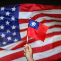 An anti-government protester holds a Taiwan national flag as a U.S. flag flutters in the background during a demonstration to celebrate Taiwan's National Day at Harbour City in the Tsim Sha Tsui district in Hong Kong in October 2019.   REUTERS