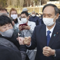Prime Minister Yoshihide Suga speaks with residents of Miyako, Iwate Prefecture, during his visit to the city Thursday. | POOL / VIA KYODO