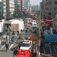 First aid stations are set up on a street above Tsukiji subway station in Tokyo in March 1995 to treat victims of a sarin nerve gas attack. | KYODO
