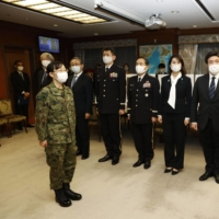 GSDF 1st Lt. Sayaka Hoshino, one of the nurses to be sent to Osaka Prefecture, meets with Defense Minister Nobuo Kishi at the Defense Ministry headquarters in Tokyo on Friday. | KYODO