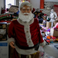 A firefighter with personal protective equipment (PPE) stands next to toys that firefighters collected throughout the year to be given to poor children on Christmas Eve, as the coronavirus pandemic continues, in Ciudad Juarez, Mexico, on Friday. | REUTERS