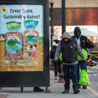 Two homeless men carry winter kits they were given by a charity in Boston on Thursday. A virus strain introduced to the U.S. at a Biogen conference in February later made its way to Boston-area homeless shelters. | AFP-JIJI