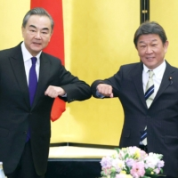 Foreign Minister Toshimitsu Motegi (right) greets his Chinese counterpart Wang Yi in Tokyo in November. | POOL / VIA KYODO