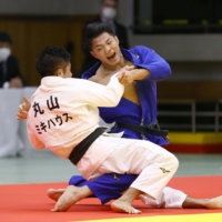 Hifumi Abe (right) defeats Joshiro Maruyama in a playoff to clinch a berth in the 66-kg division of the Tokyo 2020 judo competition on Sunday at the Kodokan Judo Institute. | HANDOUT / VIA KYODO